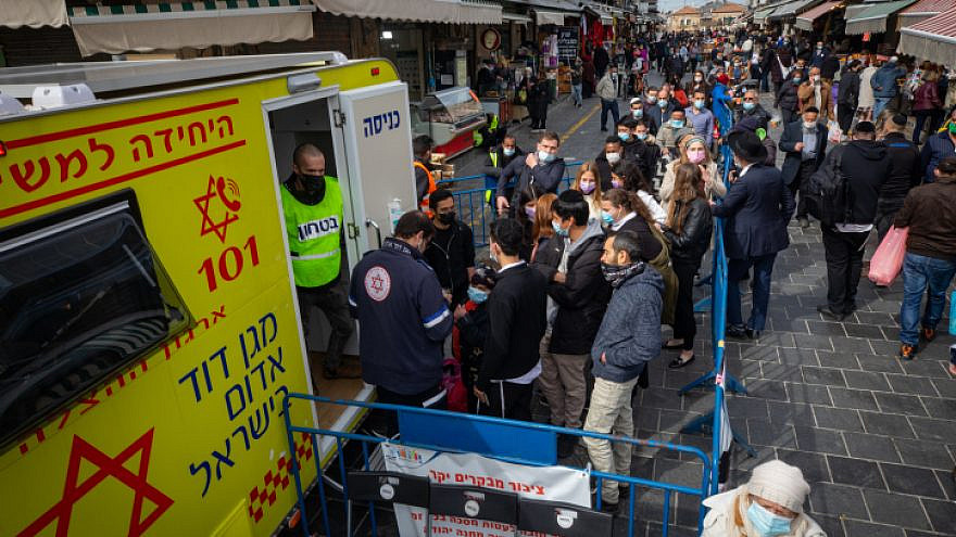 Israelis get vaccinated against COVID-19 at a mobile Magen David Adom station in Jerusalem's Machane Yehuda open-air market on Feb. 22, 2021. Photo by Olivier Fitoussi/Flash90.