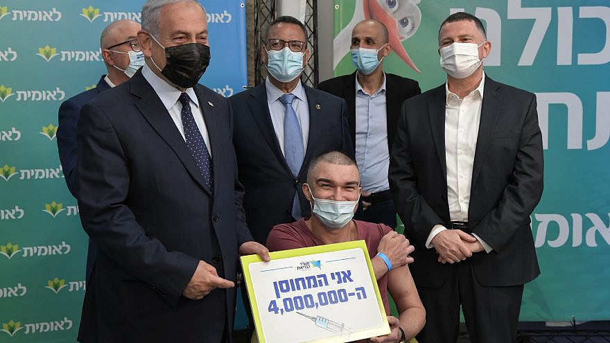 Israeli Prime Minister Benjamin Netanyahu (left) with Health Minister Yuli Edelsten (far right) and the 4,000,000th Israeli vaccinated against COVID-19 on Feb.16, 2021. Credit: Koby Gideon/GPO.