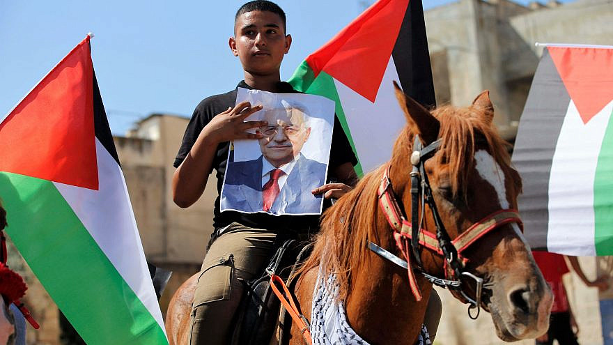 A Palestinian boy holds a poster in support of Palestinian Authority leader Mahmoud Abbas in the West Bank town of Tubas on Sept. 27, 2020. Photo by Nasser Ishtayeh/Flash90.