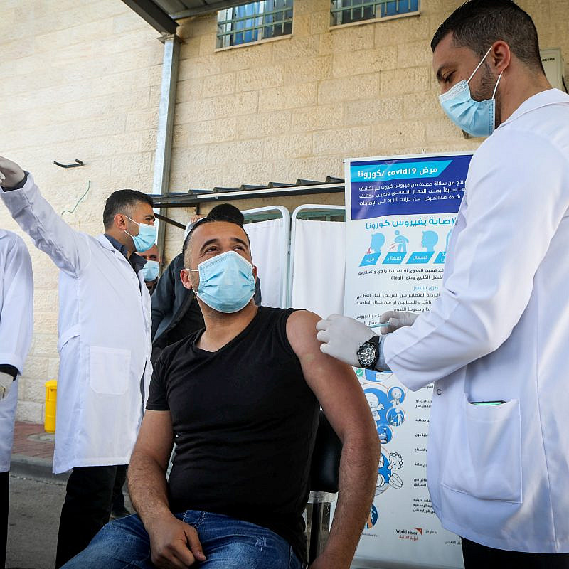 Palestinian health workers  in the West Bank city of Bethlehem are vaccinated against COVID-19 after a delivery of vaccine doses arrives from Israel on Feb. 3, 2021. Photo by Wisam Hashlamoun/Flash90.