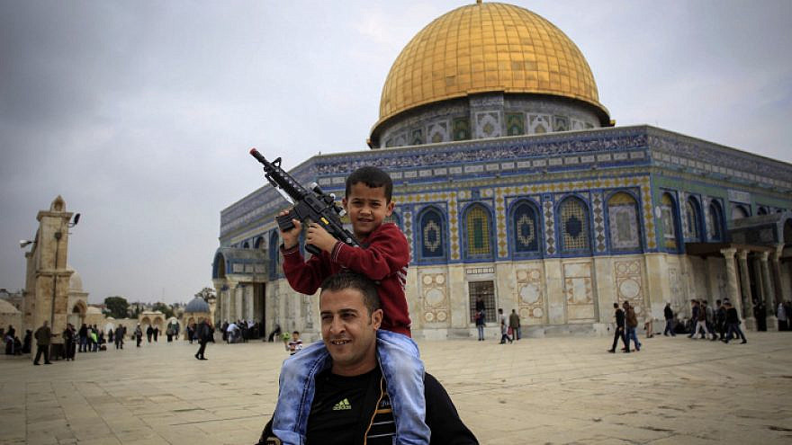 A Palestinian child plays with a toy gun on his father's shoulders at the Al Aqsa Mosque compound in Jerusalem's Old City, Nov. 6, 2015. Photo by Muammar Awad/Flash90.