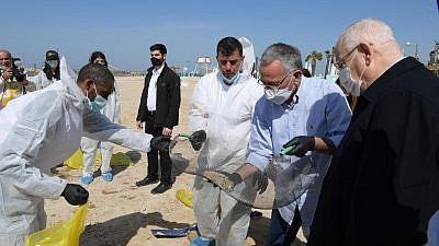 Israeli President Reuvan Rivlin (far right) visits a beach in Herzliya polluted with tar with Herzliya Mayor Moshe Fadlon (second from right), Feb. 22, 2021. Credit: Amos Ben Gershom/GPO.
