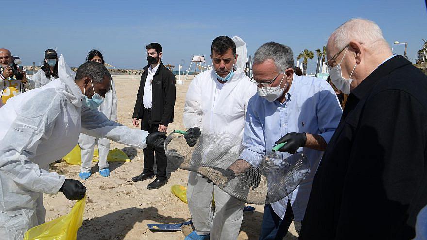 Israeli President Reuvan Rivlin (far right) visits a beach in Herzliya polluted with tar with Herzliya Mayor Moshe Fadlon (second from right), Feb. 22, 2021. Credit: Amos Ben Gershom/GPO.