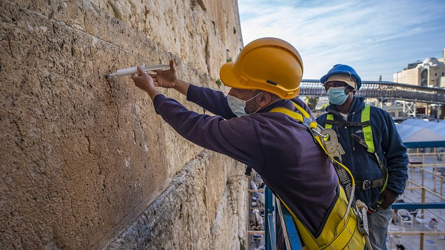 Workers inject liquid grouting into stones of the Western Wall that need strengthening in February of 2021. Credit: Israel Antiquities Authority.