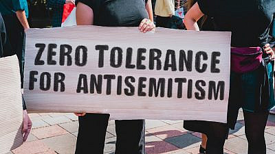 A woman holds a sign opposing anti-Semitism at a rally. Credit: AndriiKoval/Shutterstock.
