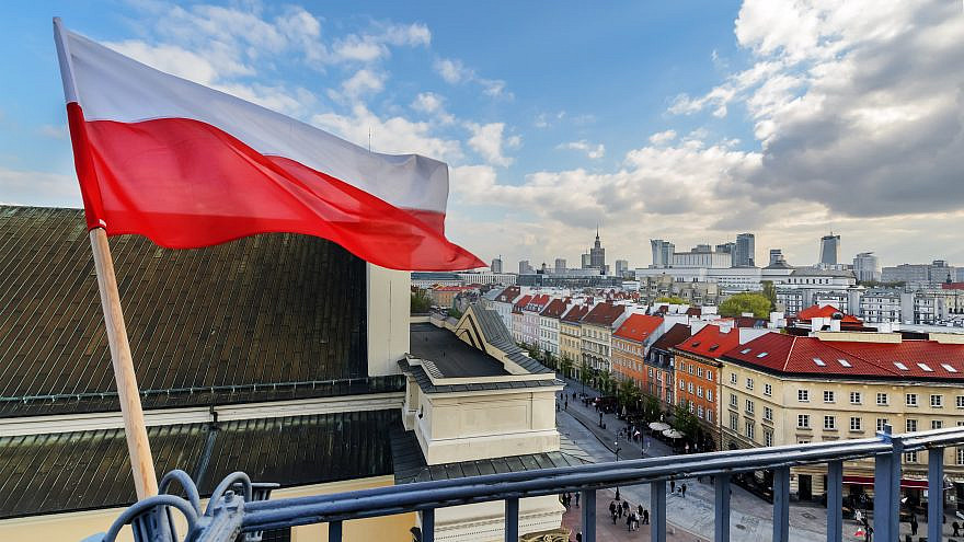The Polish flag with Warsaw in the background. Credit:  Velishchuk Yevhen/Shutterstock.