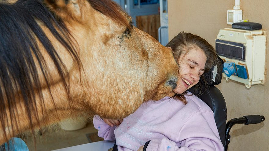 An ADI resident with severe disabilities interacts with a horse at the Judah Hertz Safari Petting Zoo and Therapeutic Horse Farm ahead of the Virtual Memorial Ceremony and Dedication at ADI Negev-Nahalat Eran on March 14, 2021.