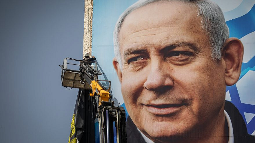 Israeli workers hang campaign posters of Prime Minister Benjamin Netanyahu, as part of the Likud election campaign, in Jerusalem on March 10, 2021. Photo by Yonatan Sindel/Flash90.