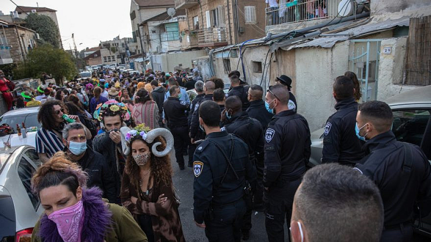 Israeli police officers close a Purim street party in Jerusalem to prevent the spread of COVID-19, Feb. 28, 2021. Photo by Olivier Fitoussi/Flash90.