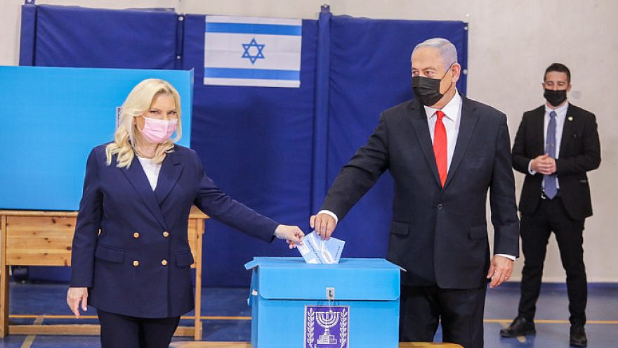 Israeli Prime Minister and head of the Likud Party Benjamin Netanyahu casts his vote in the fourth elections in two years, together with his wife, Sara Netanyahu, at a voting station in Jerusalem, on March 23, 2021. Photo by Marc Israel Sellem/POOL.