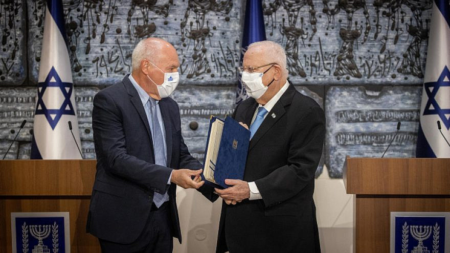 Israeli President Reuven Rivlin receives the official election results from the head of the Israeli electoral committee, judge Uzi Vogelman, during a ceremony at the President's Residence in Jerusalem on March 31, 2021. Photo by Yonatan Sindel/Flash90.