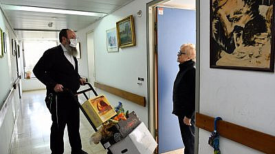 Rabbi Menachem Traxler, director of volunteering for Colel Chabad, makes his way up the stairs with a handtruck to deliver food to the elderly and homebound in Israel. Credit: Mendy Hechtman.