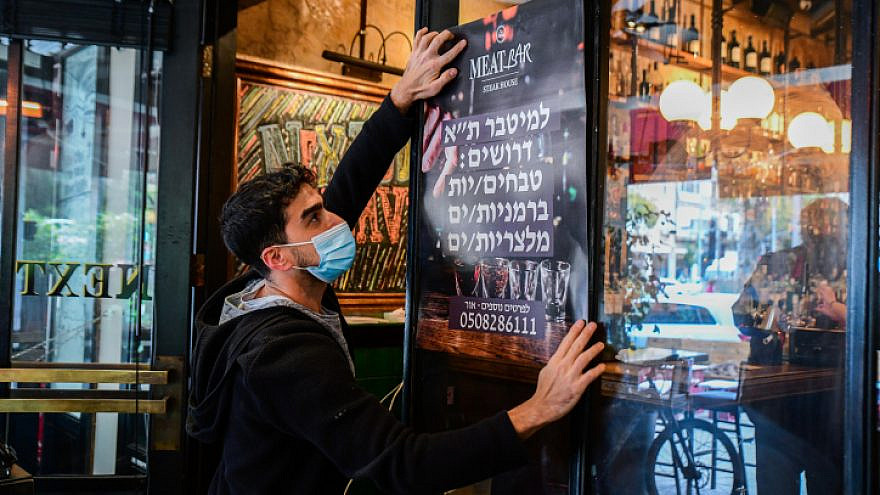 A worker in Tel Aviv prepares for the opening of restaurants in Israel, March 3, 2021. Photo by Avshalom Sassoni/Flash90.