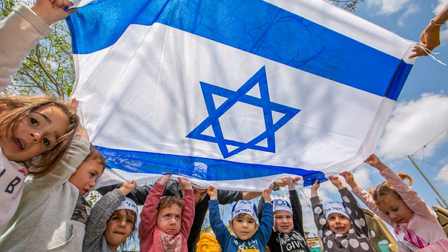 Israeli children hold Israeli flags ahead of the country's 73rd Independence Day, at a kindergarten in Moshav Yashresh, April 13, 2021. Photo by Yossi Aloni/Flash90.