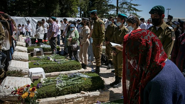 People stand still next to the graves of fallen soldiers at the Mount Herzl cemetery in Jerusalem as a two-minute siren sounds, marking Israel's Memorial Day, April 14, 2021. Photo by Olivier Fitoussi/Flash90.