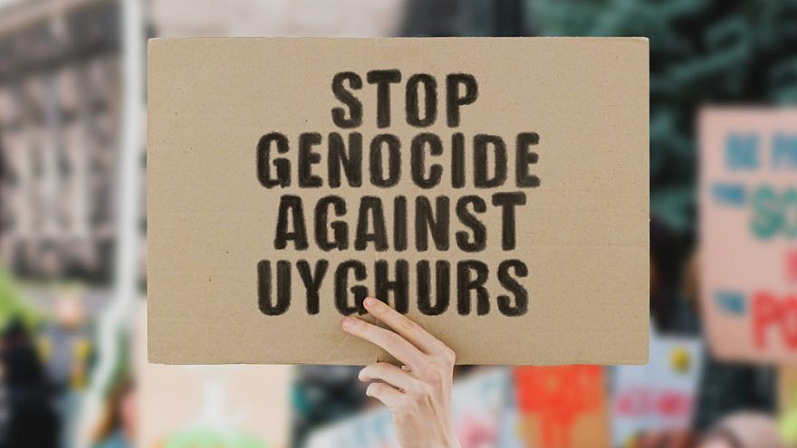 A man holds up a sign protesting the genocide against Uyghur Muslims by the Chinese government. Credit: AndriiKoval/Shutterstock.