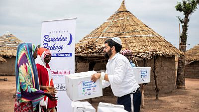 Rabbi Israel Uzan of Chabad Lubavitch of Nigeria hands out a box of food for use at the end of Ramadan. Credit: Chabad Lubavitch of Nigeria.