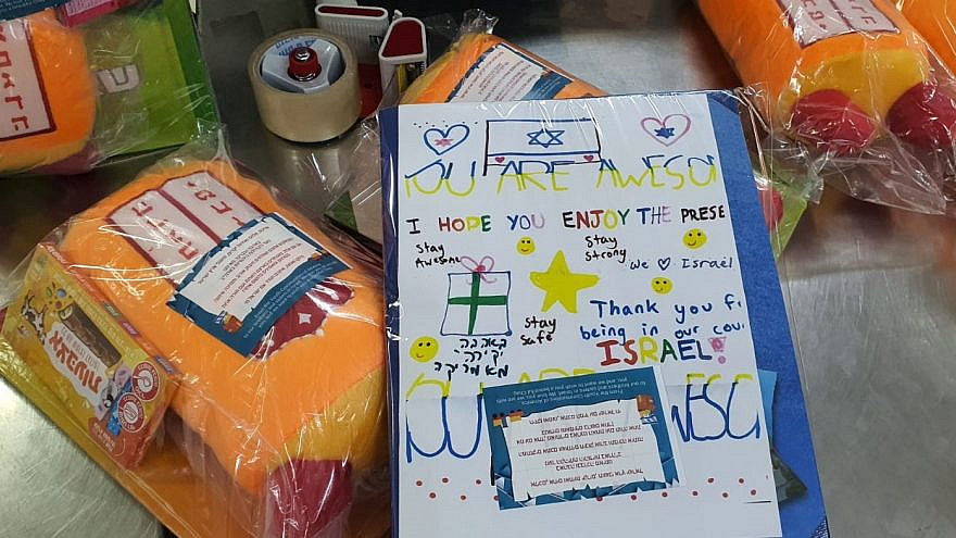 Gifts for children taking shelter from the barrage of rockets that have been fired at Israel from the Gaza Strip were assembled at the Pantry Packers Volunteer Center in Jerusalem and included handwritten notes from day-school students in the United States. Credit: Courtesy.