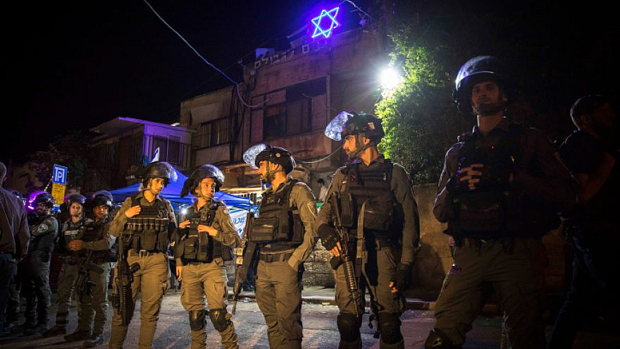Israeli border police stand guard by a house of a Jewish family during a protest against Israel's plan to demolish some houses of Palestinians in the eastern Jerusalem neighborhood of Sheikh Jarrah, May 6, 2021. Photo by Olivier Fitoussi/Flash90.