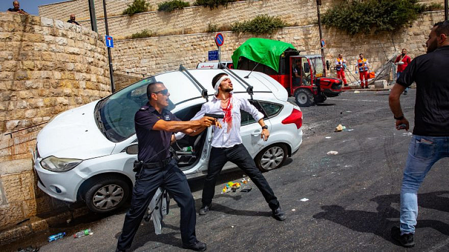 An Israeli policeman fends off an angry Arab mob swarming an Israeli motorist, pelting his car with stones and driving him off the road, outside Jerusalem's Old City, May 10, 2021. Photo by Olivier Fitoussi/Flash90.