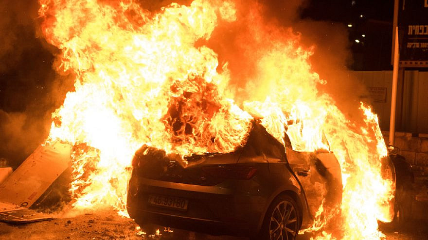 A car burns during violent riots in Akko on May 12, 2021. Photo by Roni Ofer/Flash90.