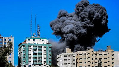 Smoke rising from the Al-Jalaa tower in Gaza City after an Israeli airstrike, which according to the Israel Defense Forces housed Hamas intelligence and weaponry, in the midst of a conflict with Israel. Several media outlets also had offices in the building, including the Associated Press and Al Jazeera, May 15, 2021. Photo by Atia Mohammed/Flash90.