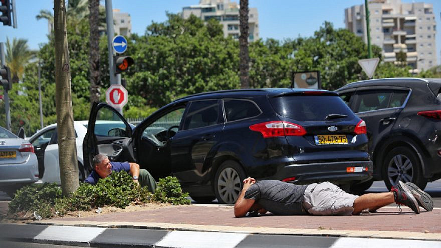 Israelis take cover in Ashkelon as a Red Alert siren warns of incoming rockets from the Gaza Strip, May 19, 2021. Photo by Edi Israel/Flash90.