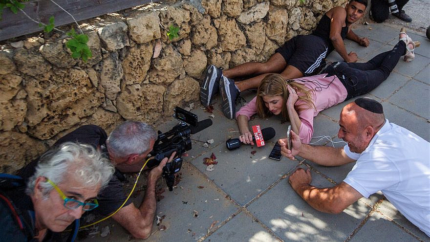 Members of the press take cover as a Red Alert siren sounds a warning of incoming rockets fired from the Gaza Strip into Ashkelon in southern Israel, May 20, 2021. Photo by Edi Israel/Flash90.