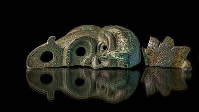 A rare bronze oil lamp, shaped like a grotesque face cut in half, was discovered during excavations in Jerusalem's City of David National Park, May 5, 2021. Credit: Israel Antiquities Authority.