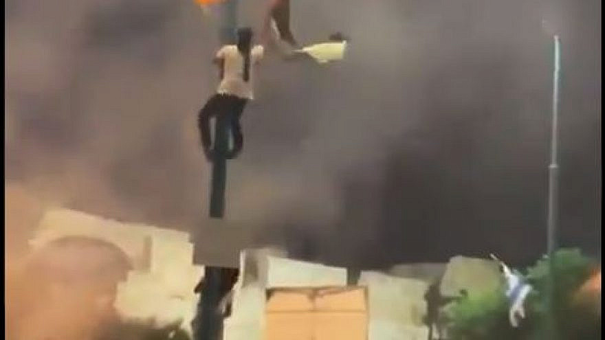 An Arab-Israeli Lod resident climbs up a pole to replace and Israeli flag with a Palestinian one, May 10, 2021. Source: Twitter/Screenshot.