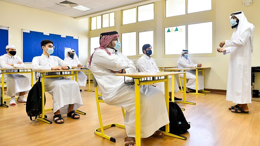 Students wearing face masks and maintaining social distancing at a classroom on the first day of school reopening at a Secondary School in Doha, Qatar. Credit: Noushad Thekkayil/Shutterstock.