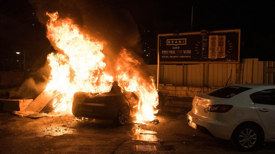 A car is set on fire during clashes between Arab and Jews in Acre, northern Israel, May 12, 2021. Photo by Roni Ofer/Flash90