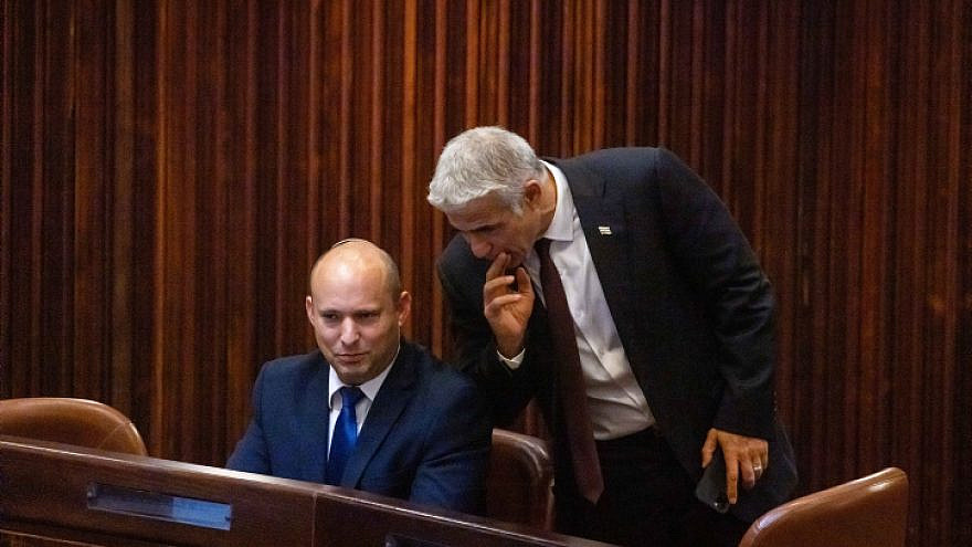 Yamina Party leader Naftali Bennett (seated) and Yesh Atid Party chairman Yair Lapid in the Knesset in Jerusalem during the election for the next Israeli president, June 2, 2021. Photo by Olivier Fitoussi/Flash90.