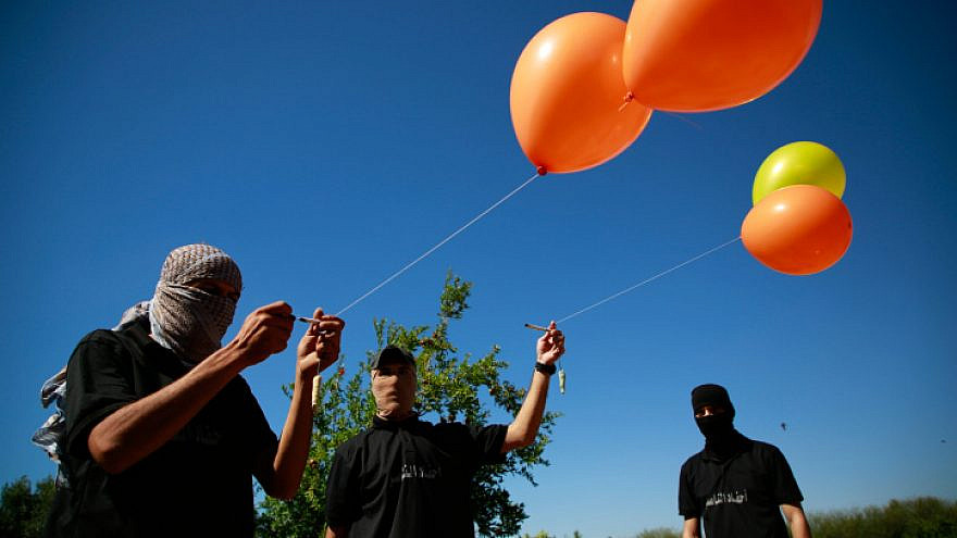 Masked Palestinian supporters of Palestinian Islamic Jihad prepare incendiary balloons east of Gaza City to launch across the border fence towards Israel, June 15, 2021. Photo by Atia Mohammed/Flash90.