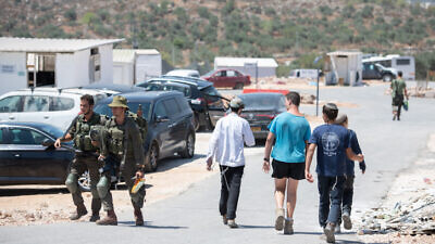 Soldiers and residents seen in the enclave of Evytar in Samaria on June 27, 2021. Photo by Sraya Diamant/Flash90