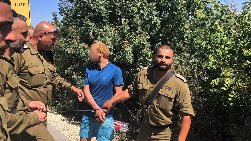 Israel Defense Forces with one of two suspects who crossed into northern Israel after they breached the Lebanese-Israeli border fence on June 7, 2021. Credit: IDF.
