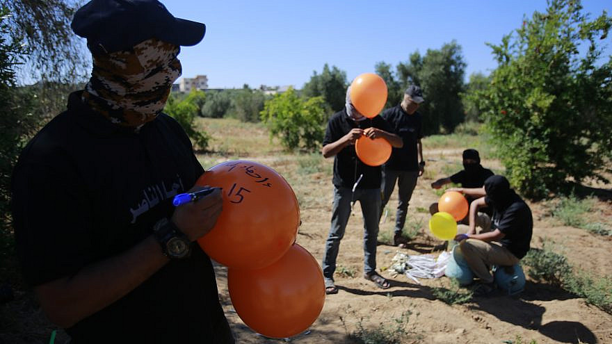 Masked supporters of Palestinian Islamic Jihad prepare incendiary balloons east of Gaza City to launch across the border fence towards Israel on June 15, 2021. Photo by Atia Mohammed/Flash90.