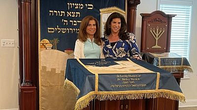 Political fundraiser Lisa Spies (right) posing for photos with her mother, Susan Wernick (left), at a private dedication event on Father's Day in front of the donations—an ark, bimah, amud—the cantor's lectern—and parochet, that she and her husband, attorney Charlie Spies made in honor of her late father, Dr. Shelley Wernick, to the Chabad Lubavitch of Alexandria-Arlington. Photo by Daniel Perez.