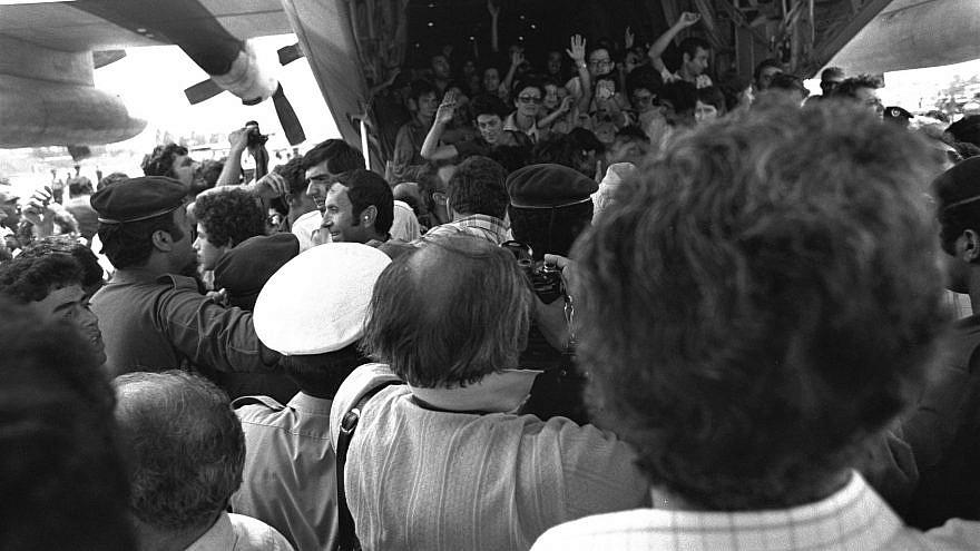 Rescued Air France passengers wave to the waiting crowd while leaving the belly of the Hercules plane at Ben-Gurion International Airport. Credit: Moshe Milner, July 4, 1976, from National Photo Collection of Israel, Photography Department, Government Press Office via Wikimedia Commons.