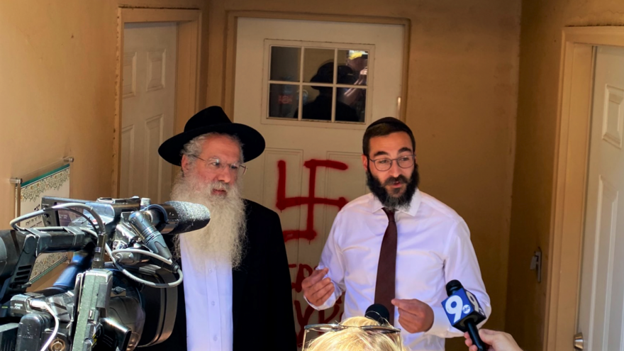 Rabbi Yossie Shemtov (left) and Rabbi Yehuda Ceitlin, both of Chabad Lubavitch of Tucson, in front of the anti-Semitic graffiti and a swastika painted on the door of Chabad on River in Tucson, Ariz., discovered on June 6, 2021. Source: Twitter.
