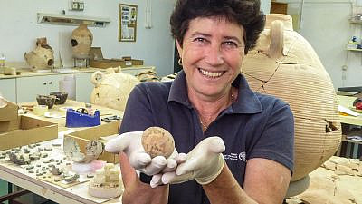 Archeologist Alla Nagorsky holding the ancient egg, June 2021. Credit: Israel Antiquities Authority.