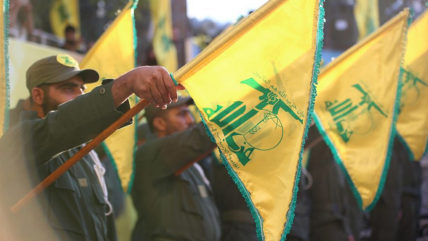 Flags of Hezbollah fly during a funeral salute. Credit: Shutterstock.