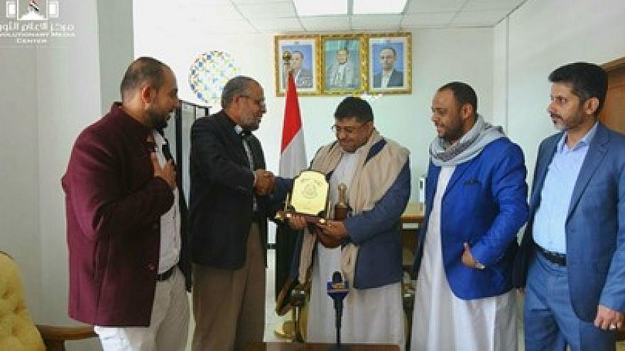 """Hamas representative in Yemen Mo'az Abu Shamala presents Muhammad Ali al-Houthi. a member of the Houthi Supreme Political Council. with a """"shield of honor"""" as a token of appreciation for the Houthis' support of the Palestinian cause, June 6, 2021. Credit: Palinfo.com via MEMRI."""