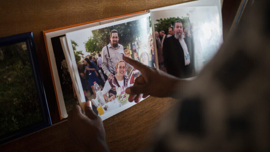 Friends and family look at pictures of Eitam and Na'ama Henkin, an Israeli couple shot and killed in Itamar, at their shiva in Jerusalem on Oct. 7, 2015. Photo by Hadas Parush/Flash90.
