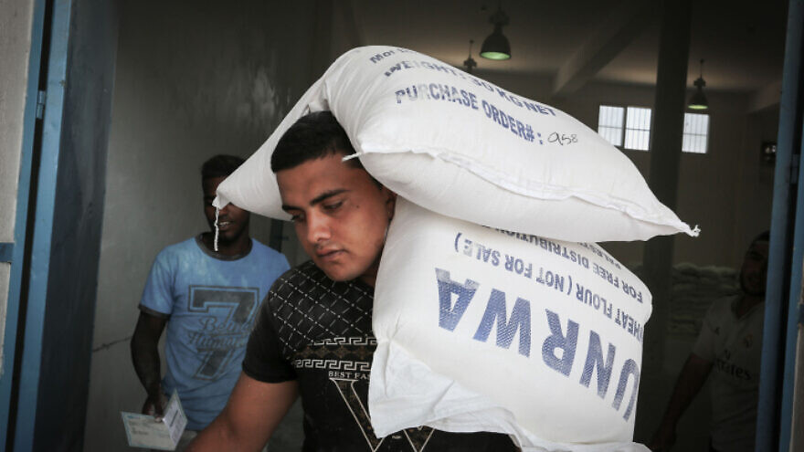 A Palestinian carries an aid package from UNRWA in Rafah in the southern Gaza Strip on Sept. 27, 2018. Photo by Abed Rahim Khatib/Flash90.