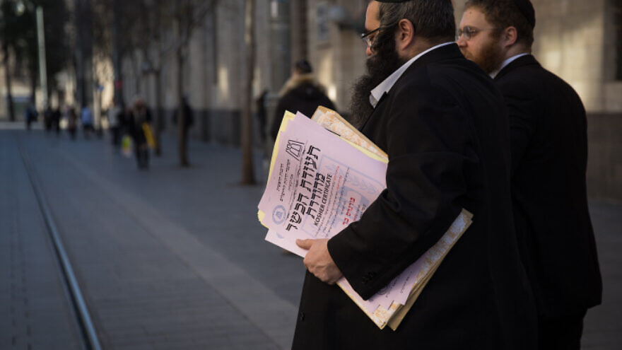 Representatives of the Chief Rabbinate of Israel deliver a kashrut certificate to a local restaurant, in central Jerusalem, on Dec. 31, 2019. Photo by Hadas Parush/Flash90.