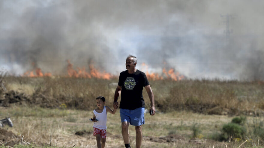 An Israeli man and child near a fire caused by shrapnel from a rocket fired from the Gaza Strip, wounding four, in Lakhish Regional Council on May 13, 2021. Photo by Gili Yaari /Flash90.