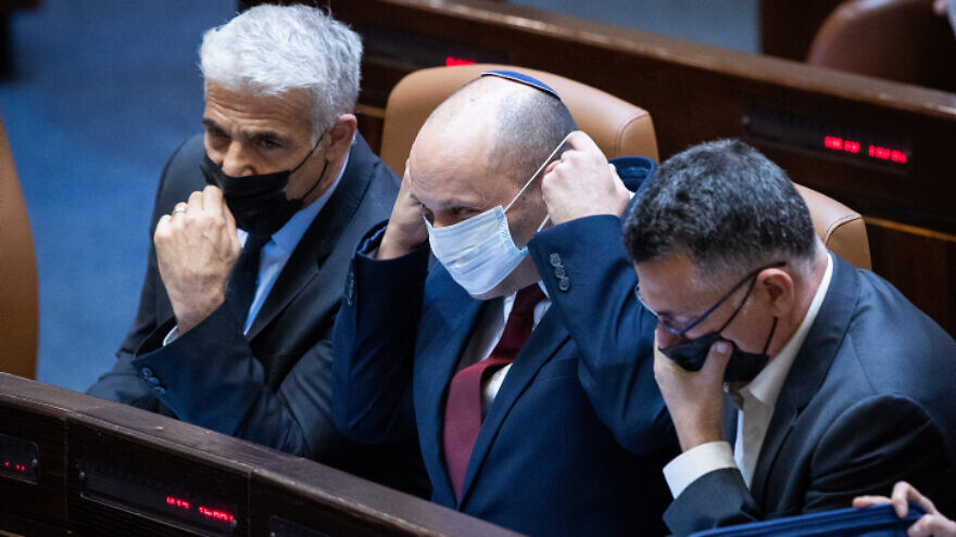From left: Israeli Foreign Minister Yair Lapid, Prime Minister Naftali Bennett and Justice Minister Gideon Sa'ar attend a Knesset session, on July 6, 2021. Photo by Yonatan Sindel/Flash90.