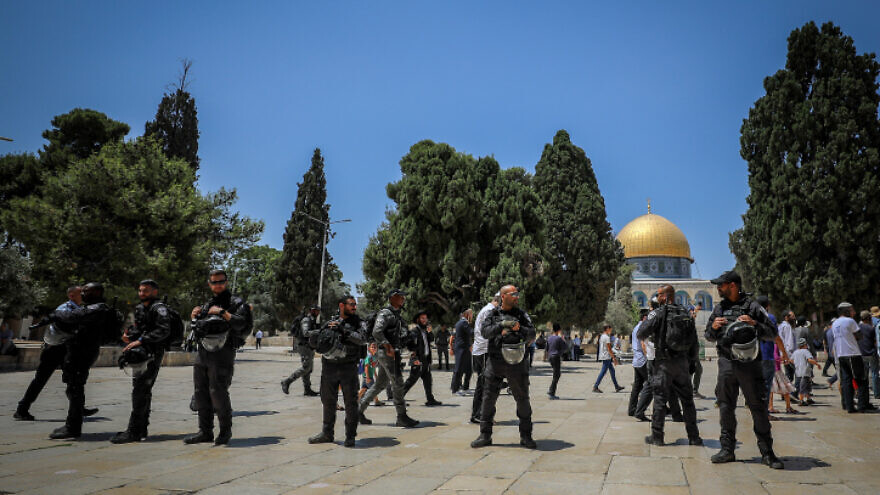 Israeli security forces guard as a group of Jewish visitors on the Temple Mount in Jerusalem's Old City, during Tisha B'Av, July 18, 2021. Photo by Jamal Awad/Flash90