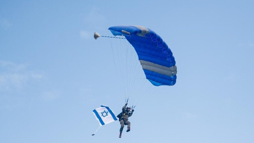 An Israeli paratrooper holding flying the flag of Israel while parachuting over Slovenia as part of commemoration of Jewish World War II paratroopers. Credit: IDF.